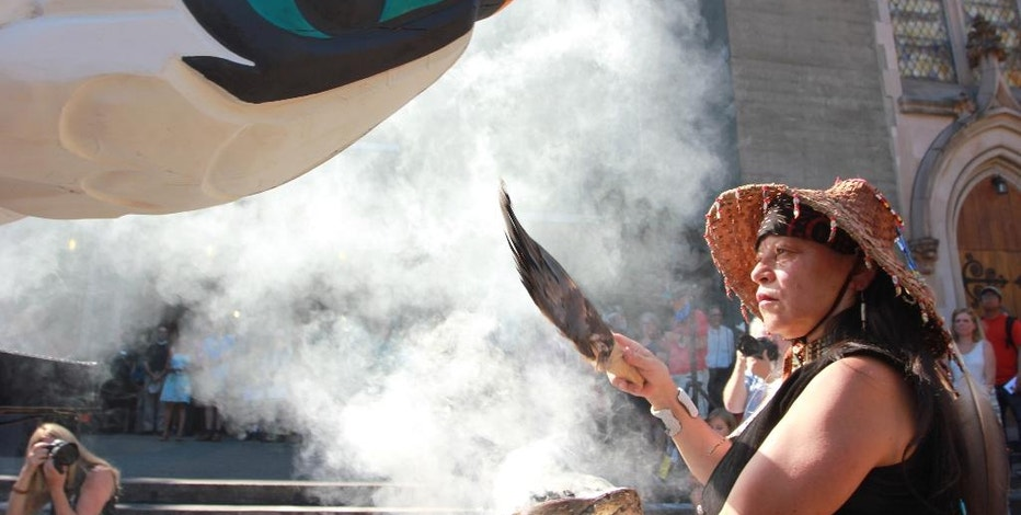 Linda Soriano of the Lummi Nation performs a smudge ceremony at Saint Mark's Episcopal Cathedral in Seattle, fanning smoke from burning sage with eagle feathers onto a totem pole, Thursday, Aug. 25, 2016. The 22-foot-tall Lummi Nation totem pole is traveling nearly 5,000 miles across the U.S. and Canada to galvanize opposition to the development of fossil fuel infrastructure, particularly around sea ports in Oregon and Washington. (AP Photo/Manuel Valdes)