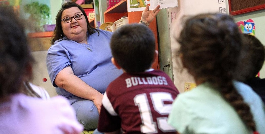 """FILE - In this Wednesday, Feb. 24, 2016, file photo, Jeannie Doler, a preschool teacher at the Kangaroo's Patch Day Care Center, reads """"Caps for Sale"""" by Esphyr Slobodkina to her students in Pontotoc, Miss. Child care is a major expense for many American families and can be difficult to manage. (Adam Robison/The Northeast Mississippi Daily Journal via AP, File)"""