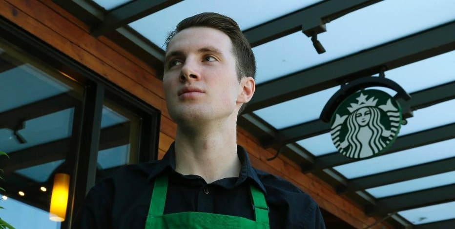 """Starbucks barista Oliver Savage poses for a photo in front of a Starbucks store near where he works Monday, Aug. 29, 2016, in Seattle. Savage is joining other workers and city leaders in pushing for new """"secure scheduling"""" rules for retail and food-service businesses with hourly employees, including requiring them to schedule shifts two weeks in advance, and offer hours to existing employees before hiring new staff. (AP Photo/Ted S. Warren)"""