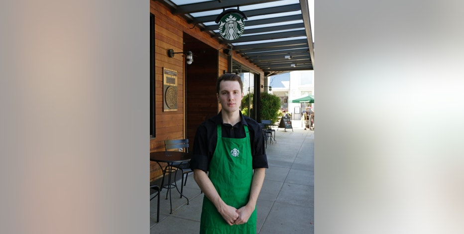 """Starbucks barista Oliver Savage poses for a photo in front of a Starbucks store near where he works, Monday, Aug. 29, 2016, in Seattle. Savage is joining other workers and city leaders in pushing for new """"secure scheduling"""" rules for retail and food-service businesses with hourly employees, including requiring them to schedule shifts two weeks in advance, and offer hours to existing employees before hiring new staff. (AP Photo/Ted S. Warren)"""