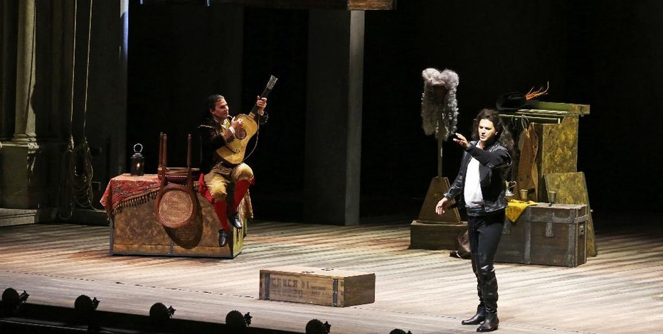 """Massimo Cavalletti, left, performs the role of Figaro as Bogdan Mihai, right, plays the role of Il Conte d'Almaviva and Rocío Ignacio, above, performs the role of Rosina in a dress rehearsal of """"The Barber of Seville"""" at the new Dubai Opera in Dubai, United Arab Emirates, on Tuesday, Aug. 30, 2016. The comic opera will be performed in September at the new opera house, which opens Wednesday night with a performance by tenor Plácido Domingo. (AP Photo/Jon Gambrell)"""