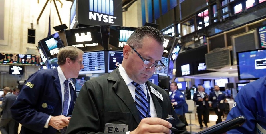 Trader Edward Curran, center, works on the floor of the New York Stock Exchange, Wednesday, Aug. 31, 2016. Stocks are opening slightly lower on Wall Street as a thin batch of earnings gave investors little to get excited about. (AP Photo/Richard Drew)