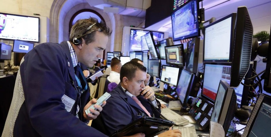 Trader Gregory Rowe, left, works with colleagues on the floor of the New York Stock Exchange, Wednesday, Aug. 31, 2016. Stocks are opening slightly lower on Wall Street as a thin batch of earnings gave investors little to get excited about. (AP Photo/Richard Drew)