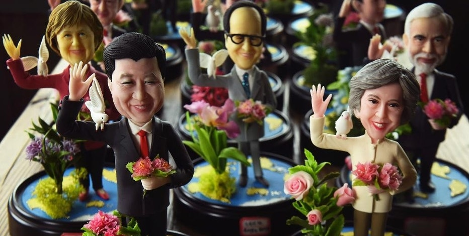 In this Sunday, Aug. 28, 2016 photo, clay figures front role from right featuring Britain's Prime Minister Theresa May next to Chinese President Xi Jinping, and other G20 leaders made by a female artist Wu Xiaoli on display at a shop to mark the upcoming G20 Summit held in Hangzhou in east China's Zhejiang province. On her first visit to China as Britain's prime minister, Theresa May will try to reassure Beijing that she wants to strengthen ties despite her delay on a decision over whether to approve a Chinese-backed nuclear power plant in southwestern England. (Chinatopix via AP)
