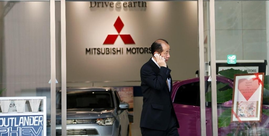 FILE - In this Feb . 5, 2013 file photo, a man talking on the mobile phone walks out from the headquarters of Mitsubishi Motors Corp. in Tokyo. Japanese transport ministry officials raided the Tokyo headquarters of scandal-ridden Mitsubishi Motors Corp. Friday, Sept. 2, 2016 after the government alleged the automaker cheated on mileage ratings on more models than earlier reported. (AP Photo/Koji Sasahara, File)