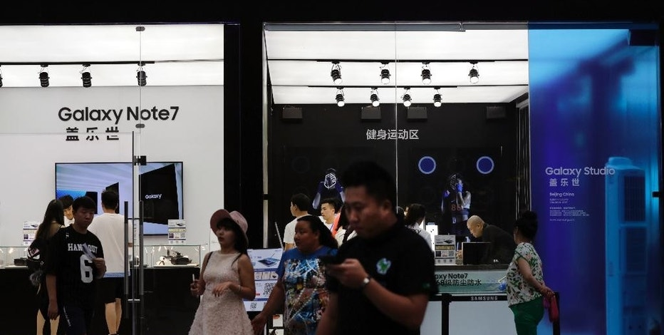 Chinese people visit the Samsung roadshow booth promoting their latest Galaxy Note 7 smartphone, outside a shopping mall in Beijing, Thursday, Sept. 1, 2016. Samsung has delayed shipments of Galaxy Note 7 smartphones in South Korea for quality control testing after reports that batteries in some of the jumbo smartphones exploded while they were being charged. (AP Photo/Andy Wong)