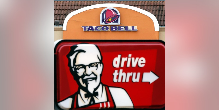 FILE - This Jan. 31, 2014, file photo, shows a Taco Bell facade behind a KFC drive-thru sign in Saugus, Mass.  Yum Brands says, on Friday, Sept. 2, 2016,  it will sell a stake in its China unit, which the parent company of KFC and Pizza Hut is spinning off later this year. (AP Photo/Elise Amendola, File)