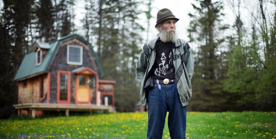 FILE-In this Friday, May 23, 2014 file photo, Burt Shavitz, co-founder of Burt's Bees, poses on his property in Parkman, Maine. The converted turkey coop in background that Shavitz once called home is going to be saved and displayed at the company's headquarters in North Carolina. Shavitz died in July 2015. (AP Photo/Robert F. Bukaty, File)