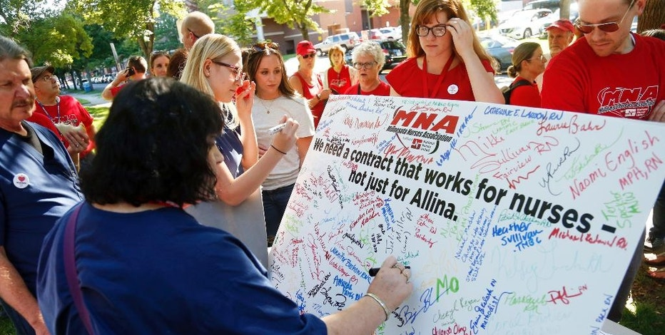 A nurse adds her signature to scores of signatures that fill a large poster of the Minnesota Nurses Associations as community, labor leaders and faith-based groups gather at Stewart Park Wednesday, Aug. 31, 2016 in Minneapolis for a rally to show support for Allina Health nurses who are scheduled to go on strike Monday, Sept. 5, unless a settlement is reached. (AP Photo/Jim Mone)