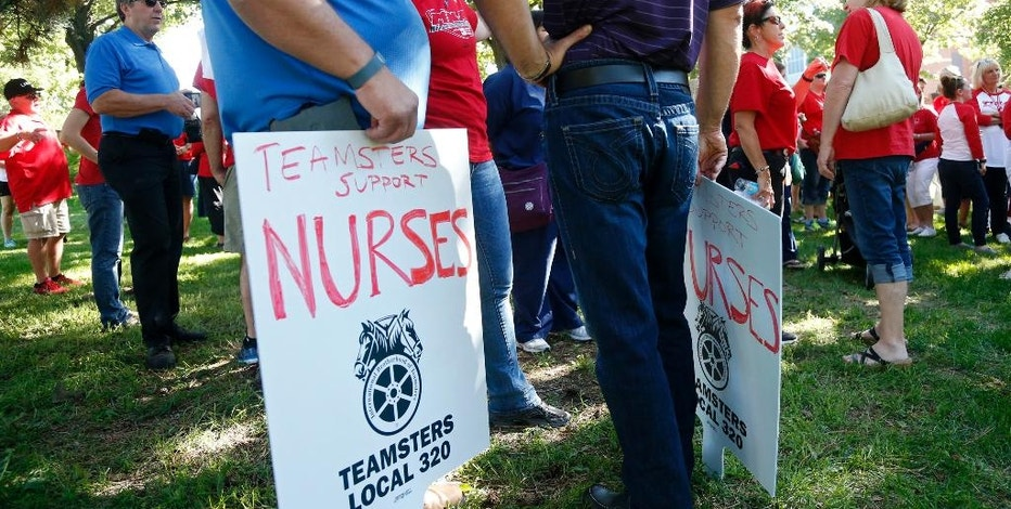 Community, labor leaders and faith-based groups gather at Stewart Park Wednesday, Aug. 31, 2016 in Minneapolis for a rally to show support for Allina Health nurses who are scheduled to go on strike Monday, Sept. 5, unless a settlement is reached. (AP Photo/Jim Mone)