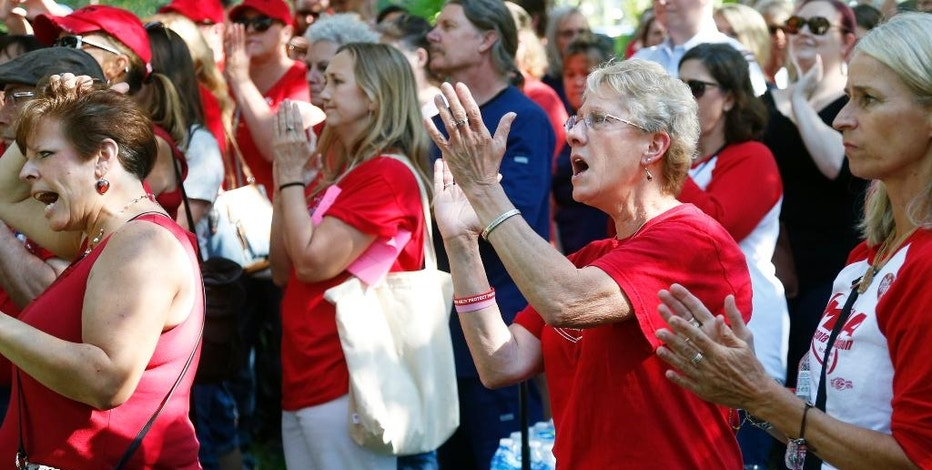 Members of the Minnesota Nurses Association applaud during a rally as community, labor leaders and faith-based groups gather at Stewart Park, Wednesday, Aug. 31, 2016 in Minneapolis to show support for Allina Health nurses who are scheduled to go on strike Monday, Sept. 5, unless a settlement is reached. (AP Photo/Jim Mone)