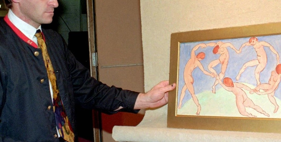 "FILE - In this Nov.30, 1995 file photo, an unidentified employee of the Drouot auction house looks at the painting ""La Danse"" (The Danse) by French artist Henri Matisse in Paris. Four Paris auctioneers and dozens of auction workers are awaiting Tuesday Sept. 6, 2016 a verdict in a vast alleged scam to steal thousands of artworks and other valuable items worth millions of euros over several years. (AP Photo/Jacques Brinon, File)"