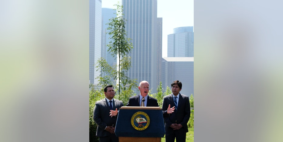 Calif., Gov. Jerry Brown, center, flanked by Senate President pro tempore Kevin de Leon, D-Los Angeles, right, and Assemblyman Eduardo Garcia, D-Coachella, left, speaks during a news conference prior to signing legislation in Los Angeles on Thursday, Sept. 8, 2016. The law sets a new goal to reduce greenhouse gas emissions 40 percent below 1990 levels by 2030. (AP Photo/Richard Vogel)