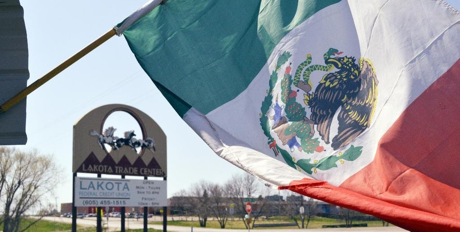 FILE - In this May 1, 2015 file photo, a Mexican flag flies outside La India Bonita Mexican Restaurant in front of the Lakota Trade Center in Kyle, S.D., on the Pine Ridge Indian Reservation. The population growth of U.S. Latinos is slowing thanks to lower immigration and declining birthrates, although states like North Dakota, South Dakota, and Tennessee are seeing Latino population spikes, according to a Pew Research Center study released Thursday, Sept. 8, 2016. (AP Photo/Russell Contreras, File)
