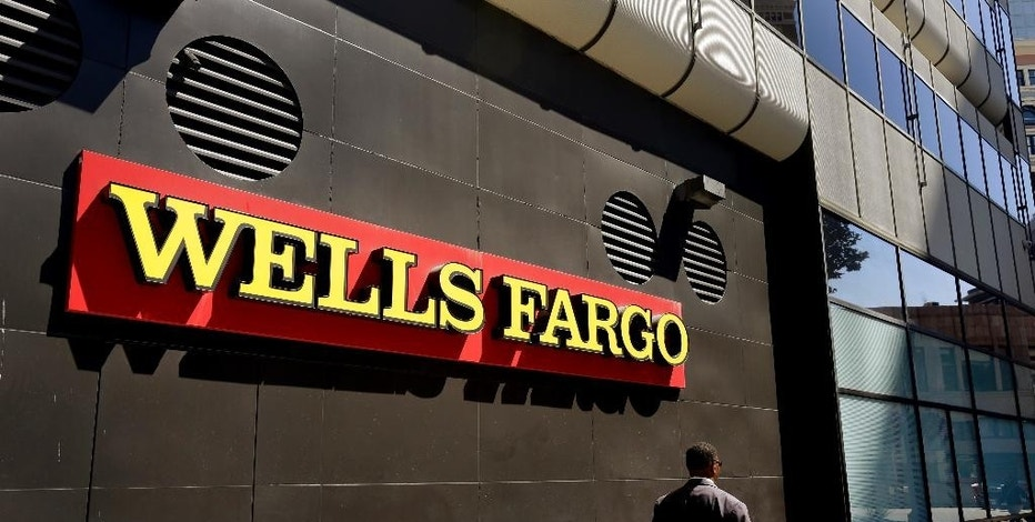 FILE - In this July 14, 2014, file photo, a man passes by a Wells Fargo bank office in Oakland, Calif. Regulators announced Thursday, Sept. 8, 2016, that Wells Fargo is being fined $185 million for illegally opening millions of unauthorized accounts for their customers in order to meet aggressive sales goals. (AP Photo/Ben Margot, File)