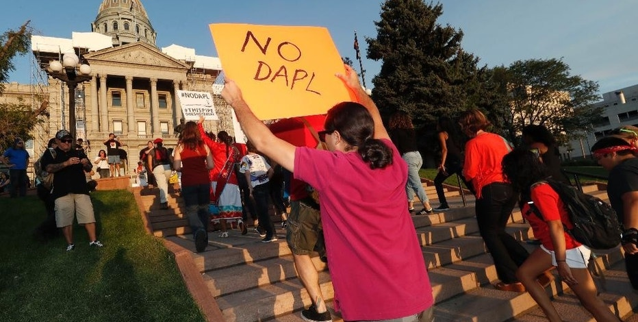 A line of protesters against the construction of the Dakota Access oil pipeline on the Standing Rock Reservation in North Dakota head to a unity rally on the west steps of the State Capitol late Thursday, Sept. 8, 2016, in Denver. Several hundred marchers walked from the four directions to the Capitol to take part in the rally against the oil pipeline. (AP Photo/David Zalubowski)