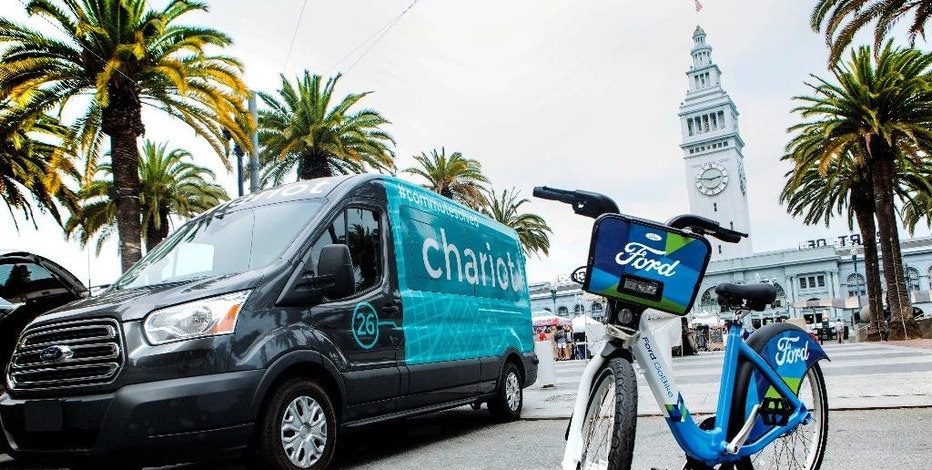 This Thursday, Sept. 8, 2016, photo taken in San Francisco and provided by Ford Motor Company shows a Ford Transit passenger van operated by Chariot shuttle service and a bicycle operated by bike-share company Motivate. Ford Motor Co. announced Friday, Sept. 9, 2016, it is buying the app-based shuttle service Chariot and is partnering with bike-share company Motivate as part of its ongoing effort to expand its traditional business. (Tommy Lau/Ford Motor Co. via AP)