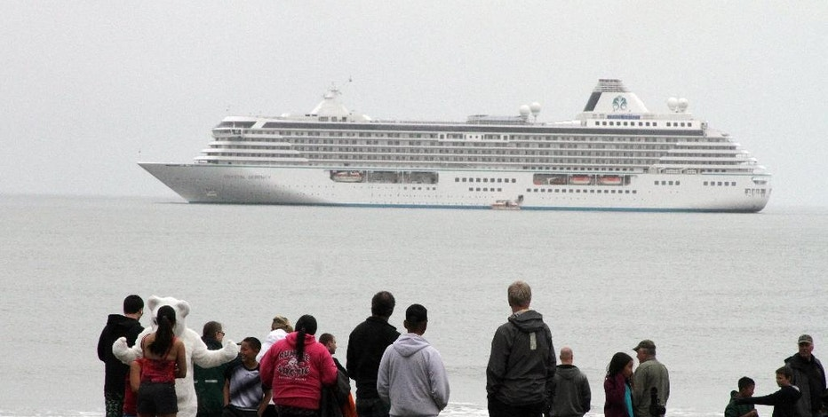 This Aug. 21, 2016, photo shows people preparing to take a polar plunge in the Bering Sea in front of the luxury cruise ship Crystal Serenity, which anchored just outside Nome, Alaska. The ship made a port call as it became the largest cruise ship to ever go through the Northwest Passage, en route to New York City. (AP Photo/Mark Thiessen)