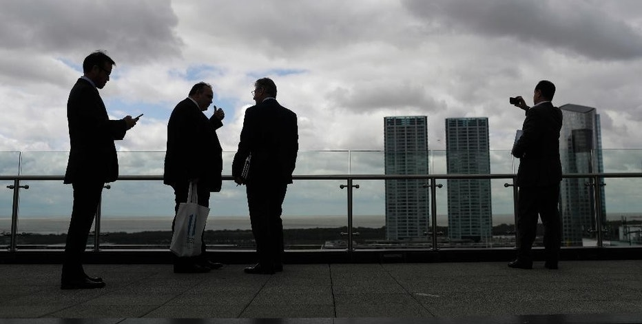 Businessmen stand on the terrace of the Kirchner Cultural Center during a break at Argentina's Business and Investment Forum in Buenos Aires, Argentina, Tuesday, Sept. 13, 2016. Over 1,500 foreign and local business leaders are participating in the three-day forum organized by the government to invest in the country's frail economy. (AP Photo/Natacha Pisarenko)
