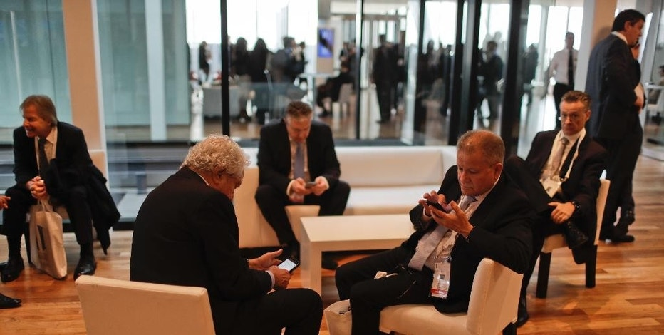 Businessmen check their phones during a break at Argentina's Business and Investment Forum in Buenos Aires, Argentina, Tuesday, Sept. 13, 2016. Over 1,500 foreign and local business leaders are participating in a three-day forum organized by the government to attract investment to the country's frail economy. (AP Photo/Natacha Pisarenko)