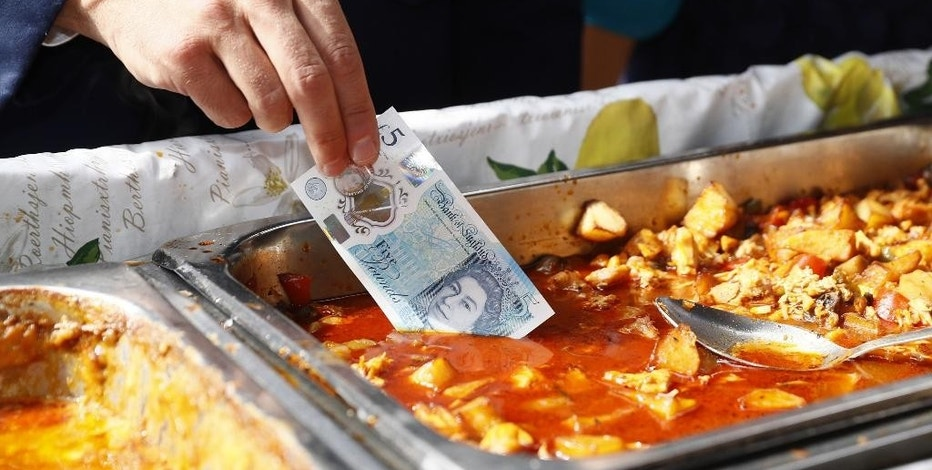Bank of England Governor Mark Carney dips a new plastic £5 note into a tray of food as he buys lunch from a stall at Whitecross Street market in London, Tuesday, Sept. 13, 2016. The polymer fiver is said by the Bank of England to be cleaner, safer and stronger than paper notes, lasting around five years longer. (Stefan Wermuth/Pool Photo via AP)