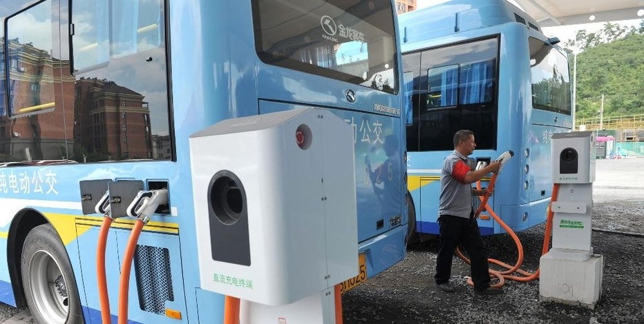In this July 15, 2016, photo, a driver charges an electric bus made by King Long United Automotive Industry at a terminal in Lin'an city in eastern China's Zhejiang Province. China's electric vehicle industry, a flagship for Beijing's technology ambitions, has been rocked by scandal after five companies were caught collecting millions of dollars in subsidies for buses they never made. (Chinatopix via AP)