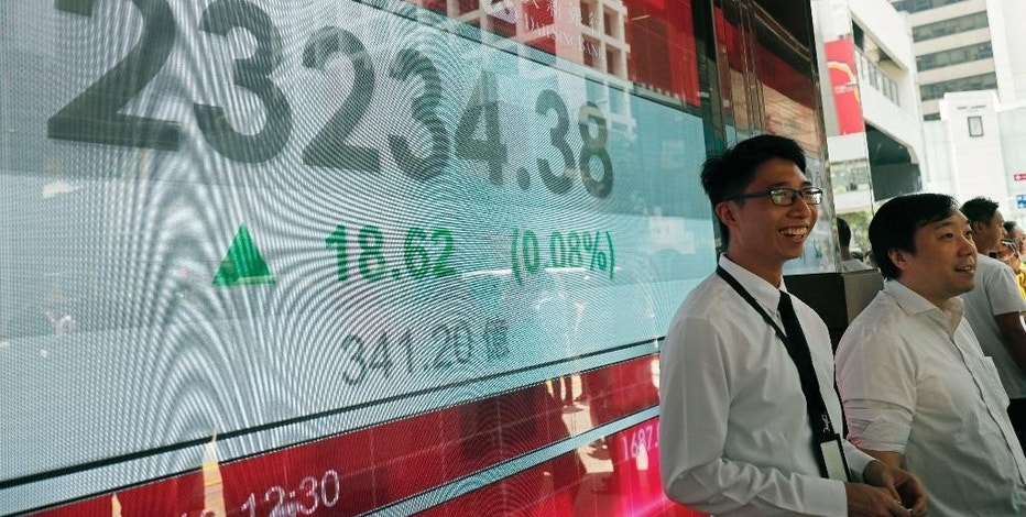 People stand next to a bank electronic board showing the Hong Kong share index at Hong Kong Stock Exchange Wednesday, Sept. 14, 2016. Global shares were mixed Wednesday, with European indexes mostly higher and Asian markets posting moderate declines. Oil prices bounced back from overnight losses. (AP Photo/Vincent Yu)