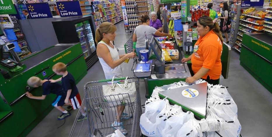 FILE - In this June 4, 2015, file photo, a customer, center, checks out at a Wal-Mart Neighborhood Market store in Bentonville, Ark. The Commerce Department releases retail sales data for August on Thursday, Sept. 15, 2016. (AP Photo/Danny Johnston, File)