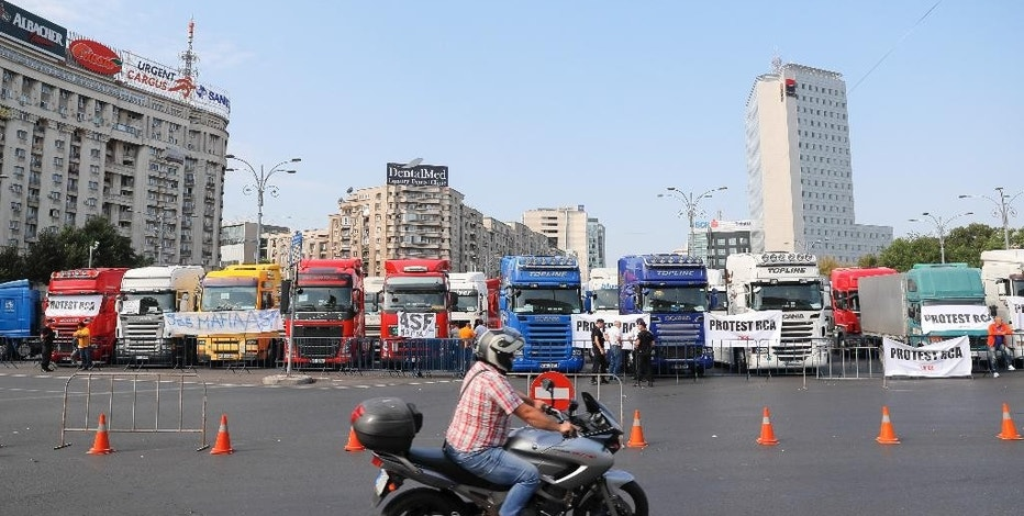 A man rides a motorcycle by trucks and taxis parked in a main square during a protest in Bucharest, Romania, Thursday, Sept. 15, 2016. Trucks and other vehicles have blocked a major square and boulevard in the Romanian capital to protest planned new insurance rates they say are too expensive and police reported traffic congestion around Romania after truck drivers drove slowly in protest. (AP Photo/Vadim Ghirda)