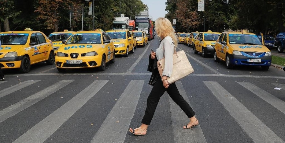 A woman walks back dropped by lines of trucks and taxis blocking a main boulevard during a protest in Bucharest, Romania, Thursday, Sept. 15, 2016. Trucks and other vehicles have blocked a major square and boulevard in the Romanian capital to protest planned new insurance rates they say are too expensive and police reported traffic congestion around Romania after truck drivers drove slowly in protest. (AP Photo/Vadim Ghirda)