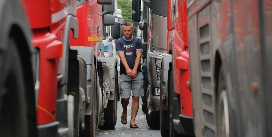 A Romanian truck driver walks between lines of trucks blocking a main boulevard during a protest in Bucharest, Romania, Thursday, Sept. 15, 2016. Trucks and other vehicles have blocked a major square and boulevard in the Romanian capital to protest planned new insurance rates they say are too expensive and police reported traffic congestion around Romania after truck drivers drove slowly in protest. (AP Photo/Vadim Ghirda)