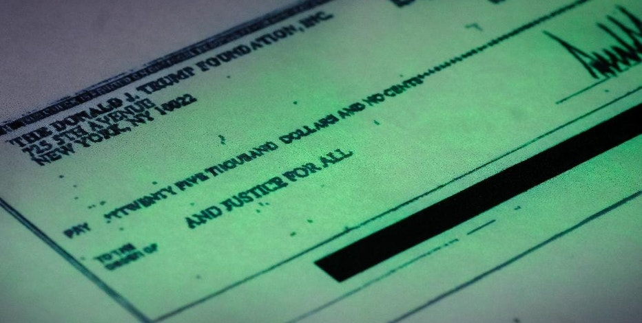 This photo made in the Associated Press Washington bureau on Thursday, Sept. 15, 2016 shows a copy of a check provided by the New York state attorney general that shows a payment of $25,000 from the Donald J. Trump Foundation to And Justice For All signed by Donald J. Trump. The $25,000 check was sent from his personal foundation to a political committee supporting Florida Attorney General Pam Bondi. Charities are barred from engaging in political activities. Trump's campaign contends that the 2013 check from the Trump Foundation was mistakenly issued following a series of clerical errors and that Trump intended to use personal funds. (AP Photo/J. David Ake)