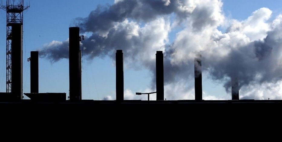 FILE - This Jan. 7, 2015, file photo, shows factory chimneys near O'Hare International Airport in Chicago. On Thursday, Sept. 15, 2016, the Federal Reserve reports on U.S. industrial production for August. (AP Photo/Nam Y. Huh, File)