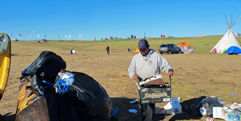 In this Wednesday, Sept. 14, 2016, photo, Dewey Plenty Chief picks up trash at a pipeline protest encampment near the Standing Rock Sioux Reservation in southern North Dakota. Plenty Chief said the camp produces several tons of trash weekly and uses several hundred gallons of water daily. (AP Photo/James MacPherson).