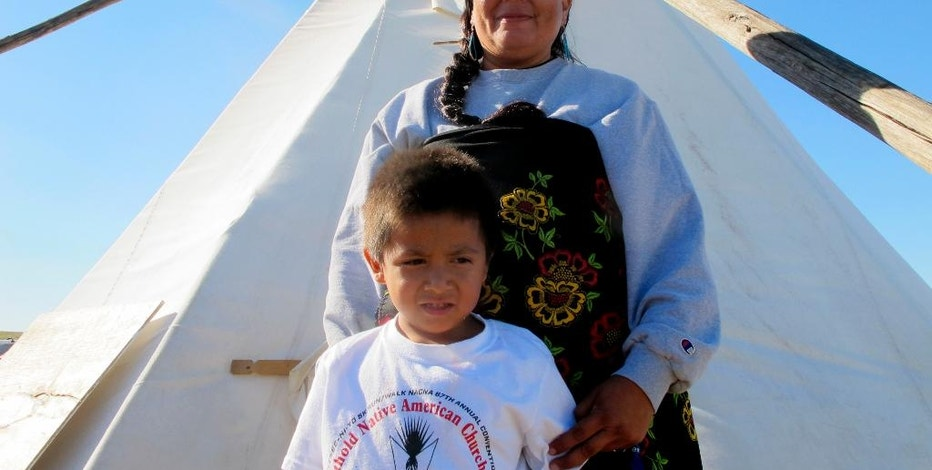 In this Wednesday, Sept. 14, 2016, photo, Melaine Stoneman, a Lakota Sioux from the Pine Ridge Reservation in South Dakota, and her 5-year-old son, Wigmuke, pose for a photo near the Standing Rock Sioux Reservation in southern North Dakota. The teepee is used as a classroom at for children whose parents have come to an encampment to oppose the construction of the Dakota Access Pipeline. (AP Photo/James MacPherson).