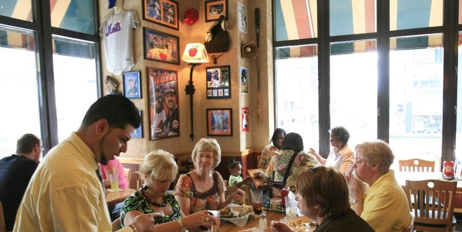 FILE - In this June 3, 2009 file photo, customers enjoy lunch at an Applebee's in New York.  Customers have been walking away from sit-down chains as convenience and affordability take precedence.  Several established restaurant groups that are retrenching, changing management or scrambling to adapt as people have more food choices all around them. (AP Photo/Mark Lennihan, file)