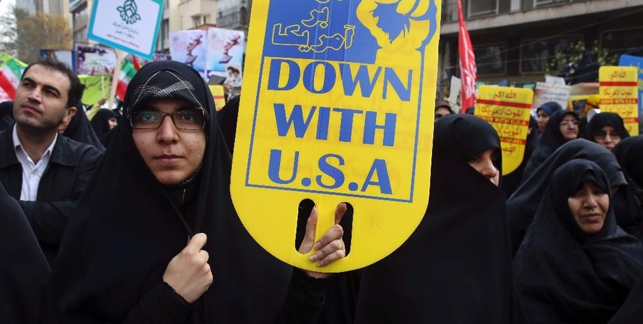 FILE - In this Nov. 4, 2015, file photo, an Iranian demonstrator holds an anti-U.S. placard during an annual rally in front of the former U.S. Embassy in Tehran. Last year's nuclear deal has removed for now the threat of a U.S.-Iranian military confrontation. But the deal rests on shaky ground. Relations between the U.S. and Iran have warmed since the agreement, to the dismay of U.S. allies like Israel and Saudi Arabia. The once hostile foes are cooperating to end Syria's civil war. Each military is staying out of the other's way as they battle the Islamic State group in Iraq. Nuclear consultations occur daily. But the next president could have his or her hands' full. The Iranians are threatening to renege unless they receive greater economic benefits. In Congress, many Republicans and even some Democrats still want the deal's collapse.(AP Photo/Vahid Salemi, file)