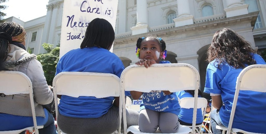 FILE - In this May 6, 2015, file photo Saryah Mitchell, sits with her mother, Teisa, Gay, left, a rally calling for increased child care subsidies at the Capitol in Sacramento, Calif. In much of the U.S., families spend more on child care for two kids than on housing. And if you're a woman, it's likely you earn less than your male colleagues even though one in four households with kids relies on mom as the sole or primary breadwinner. (AP Photo/Rich Pedroncelli, File)