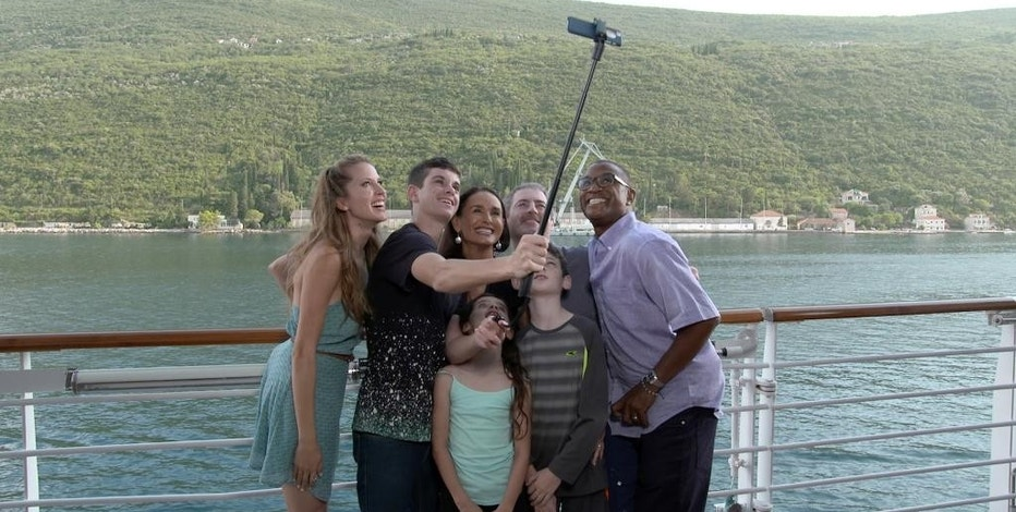 """This undated photo provided by Carnival Corporation shows hosts Andrea Feczko on the far left and Tommy Davidson on the far right taking a selfie with the Geoghegan family on a Mediterranean cruise to Greece. Feczko and Davidson are hosts of """"Vacation Creation,"""" one of three new shows produced by Carnival Corp., showcasing vacation and travel connected to cruising. """"Vacation Creation,"""" which will begin airing on The CW network this fall, features personalized vacations for individuals, couples or families who have faced hardship or are in need of hope or quality time together. (Carnival Corporation via AP)"""