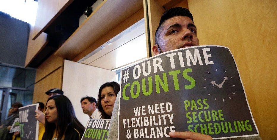 Joe Solorio, right, stands with other supporters of new work scheduling rules at a Seattle City Council meeting, Monday, Sept. 19, 2016, in Seattle. The Council was to vote Monday on new scheduling rules for hourly retail and food-service employees, including requiring employers to schedule shifts 14 days in advance and pay workers extra for certain last-minute scheduling changes. (AP Photo/Elaine Thompson)
