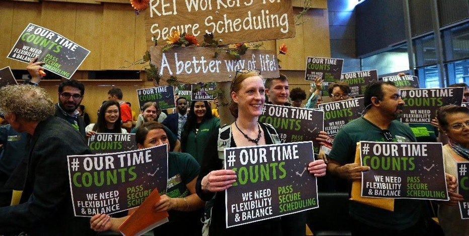 People in favor of proposed new work scheduling rules stand in support before a Seattle City Council meeting Monday, Sept. 19, 2016, in Seattle. The Council was to vote Monday on new scheduling rules for hourly retail and food-service employees, including requiring employers to schedule shifts 14 days in advance and pay workers extra for certain last-minute scheduling changes. (AP Photo/Elaine Thompson)