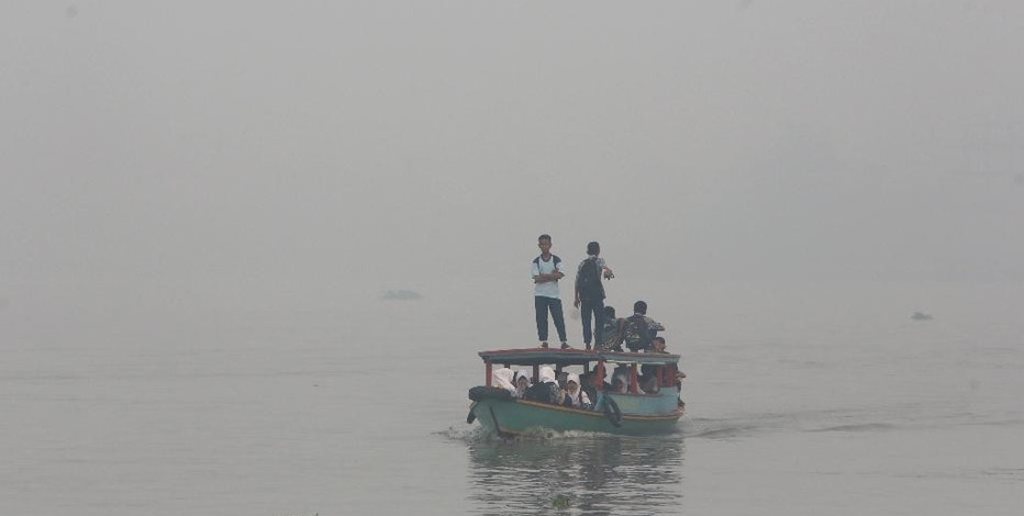 FILE - In this Thursday, Sept. 17, 2015 file photo, students ride on a boat on their way to school while haze from wildfires blanket the Musi River in Palembang, South Sumatra, Indonesia. Indonesian forest fires that choked a swath of Southeast Asia with a smoky haze for weeks in 2015 may have caused more than 100,000 premature deaths, according to new research that will add to pressure on Indonesia's government to tackle the annual crisis. (AP Photo/Tatan Syuflana, File)