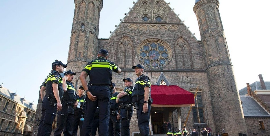 Dutch police meet outside the Knight's Hall, rear, where Dutch King Willem-Alexander is expected to read the speech outlining the Dutch government's budget plans for the year ahead in The Hague, Netherlands, Tuesday, Sept. 20, 2016. (AP Photo/Peter Dejong)