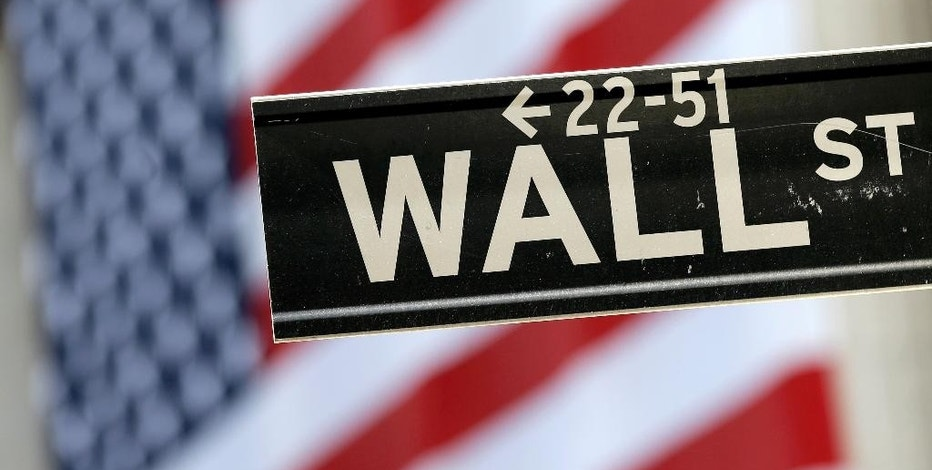 FILE - In this Tuesday, Sept. 8, 2015, file photo, a Wall Street street sign is framed by an American flag hanging on the facade of the New York Stock Exchange. The financial crisis that struck in 2008 touched off the worst recession since the 1930s Great Depression, wiping out $11 trillion in U.S. household wealth and leaving about 8 million Americans jobless. More than 5 million families lost their homes to foreclosure. Reckless trading and aggressive practices on Wall Street in the prior boom years were pinned with much of the blame. In the aftermath, Congress enacted an overhaul of financial rules aimed at preventing another meltdown and multibillion-dollar taxpayer bailout of banks. (AP Photo/Mary Altaffer, File)