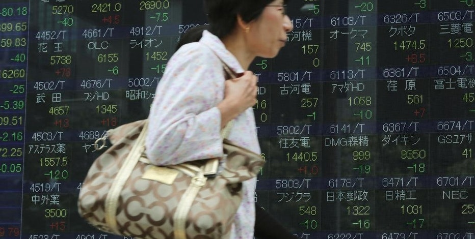 Women walks past an electronic stock board showing Japan's Nikkei 225 index at a securities firm in Tokyo, Wednesday, Sept. 21, 2016. Asian shares meandered Wednesday as markets awaited the outcomes of monetary policy meetings in the U.S. and Japan. Japan's benchmark fell after August trade data came in weaker than expected. (AP Photo/Eugene Hoshiko)