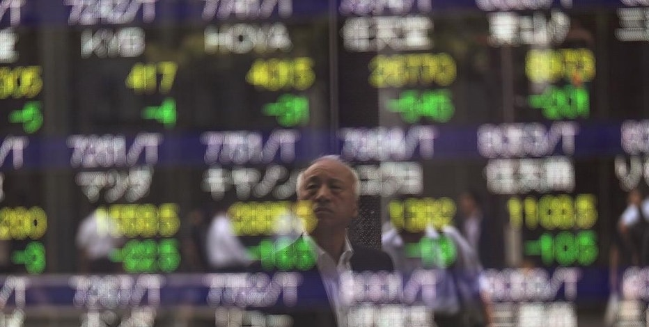 A man is reflected on an electronic stock board showing Japan's Nikkei 225 index at a securities firm in Tokyo, Wednesday, Sept. 21, 2016. Asian shares meandered Wednesday as markets awaited the outcomes of monetary policy meetings in the U.S. and Japan. Japan's benchmark fell after August trade data came in weaker than expected. (AP Photo/Eugene Hoshiko)