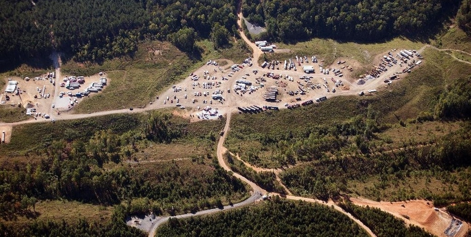 In this aerial photo, a response team works to clean a pipeline gas leak, Tuesday, Sept. 20, 2016, near Helena, Ala. A main gas line is expected to restart Wednesday with a temporary bypass after a leak and spill in Alabama led to surging fuel prices and some gas shortages across the South, a Colonial Pipeline official said Tuesday. (AP Photo/Brynn Anderson)
