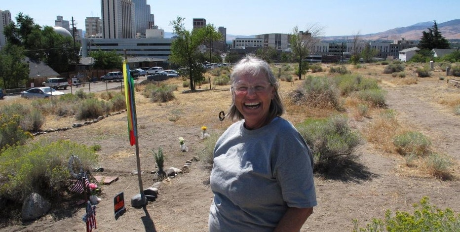 In this Sept. 10, 2016 photo, Fran Tryon, founder of the Hillside Cemetery Preservation Foundation, poses for a photo at the cemetery in Reno, Nev., next to the grave site of Paiute Chief Johnson Sides. Tryon is among those who are outraged that the owner has obtained a permit and posted a notice of plans to exhume graves and move them to make way for a development. The plan is currently on hold, but heirs of the dead remain concerned. (AP Photo/Scott Sonner)