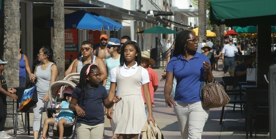 In this Wednesday, Sept. 21, 2016, photo, people walk along restaurants and retail stores at Lincoln Road Mall, in Miami Beach, Fla. On Tuesday, Sept. 27, the Conference Board releases its September index on U.S. consumer confidence. (AP Photo/Lynne Sladky)