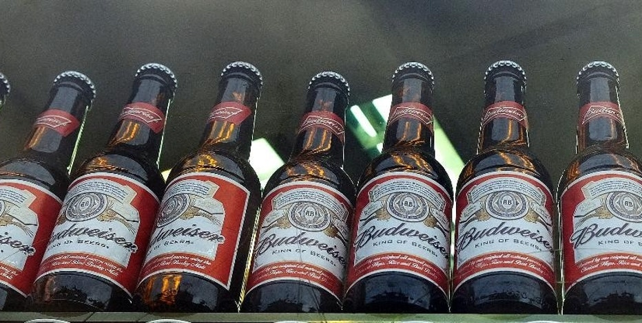 FILE - In this Tuesday, Oct. 13, 2015, file photo, bottles of Budweiser beer are on display in a shop window in London. On Wednesday, Sept. 28, 2016, it was announced that Budweiser maker Anheuser-Busch InBev will pay $6 million to the Securities and Exchange Commission to settle charges that the company made improper payments to government officials in India to promote its products and then tried to hush an employee who reported the violations. (AP Photo/Kirsty Wigglesworth, File)